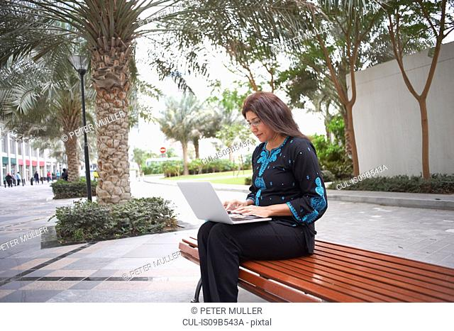 Mature businesswoman typing on laptop on park bench, Dubai, United Arab Emirates