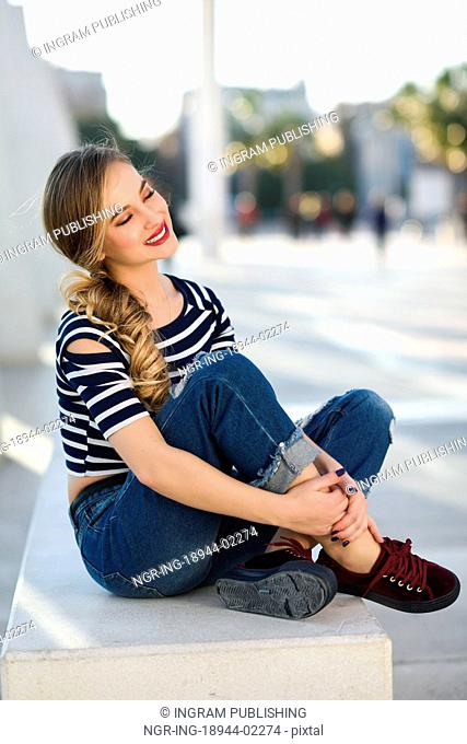 Dreamer blonde woman smiling in urban background. Beautiful young girl wearing striped t-shirt and blue jeans sitting on a bench in the street
