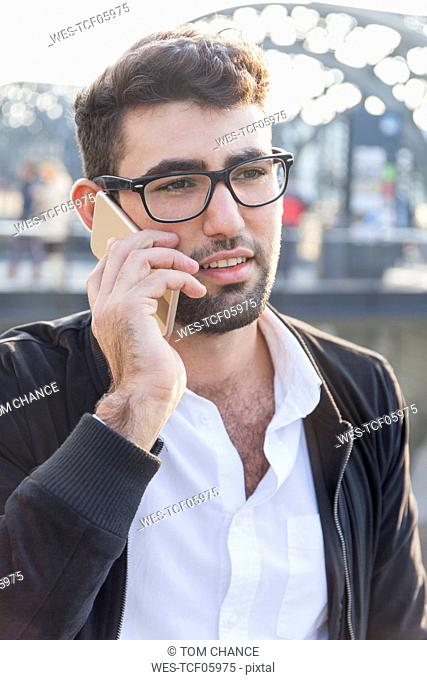 Germany, Munich, portrait of young businessman on the phone at central bus station
