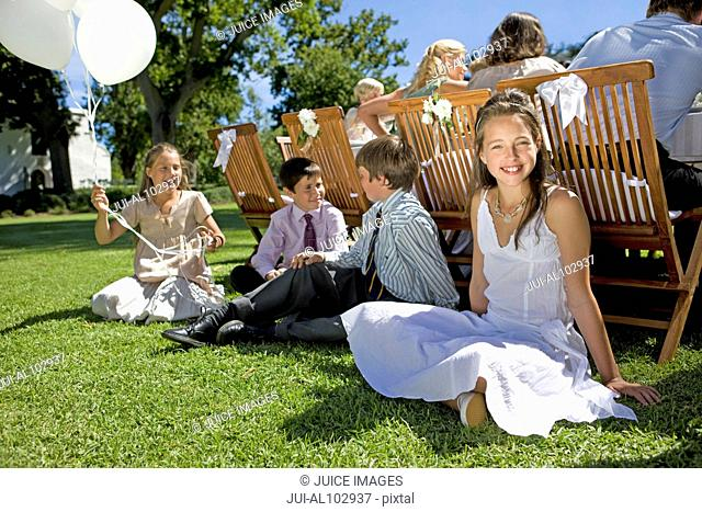 A group of young children sitting on the grass at a wedding reception