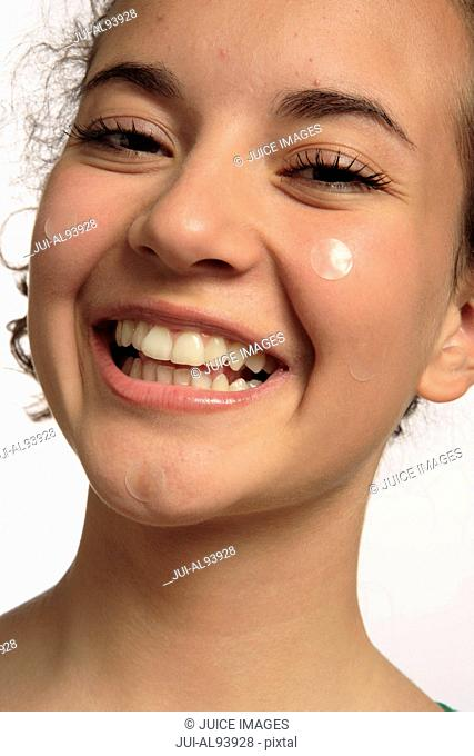 Happy portrait of girl with pimple applications on face