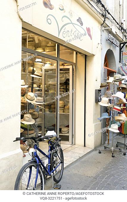 Stacks of hats, Panamas and trilbys with jolly hat stand and blue bicycle in a cobbled side street in the old quarter of L'Isle-sur-la-Sorgue, Vaucluse