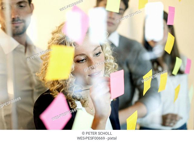 Colleagues in office behind glass pane with adhesive notes