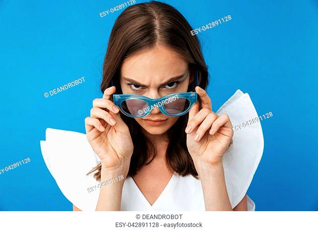 Portrait of a serious young girl in summer clothes looking over sunglasses isolated over blue background