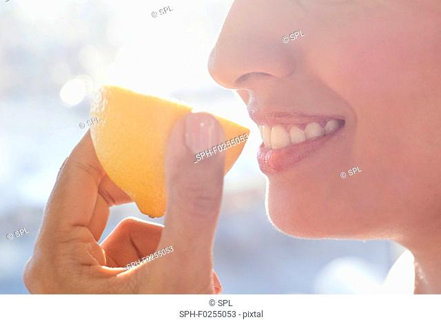 Woman holding half a lemon