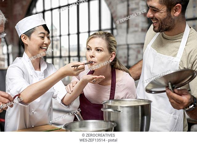Female student tasting from pot in cooking class