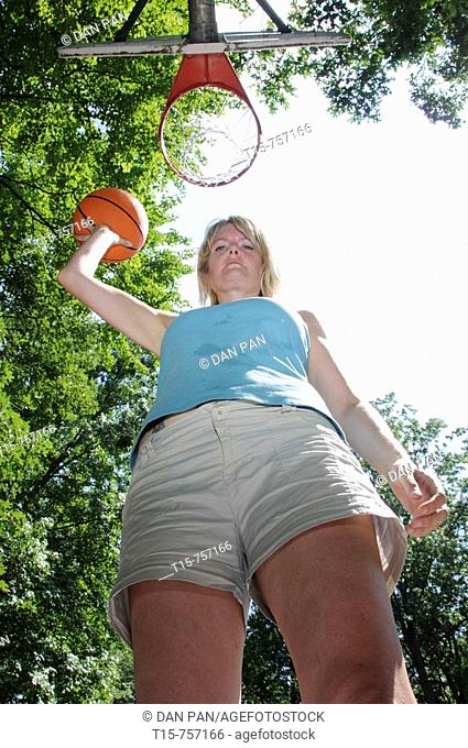 tall woman with basketball looking down