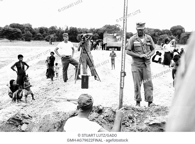 A team of surveyors from the United States military performing work, local women and children are watching the team work, Vietnam, 1967
