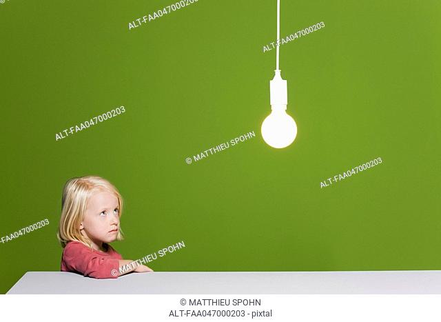 Little girl biting lip looking with concern up at illuminated light bulb suspended overhead