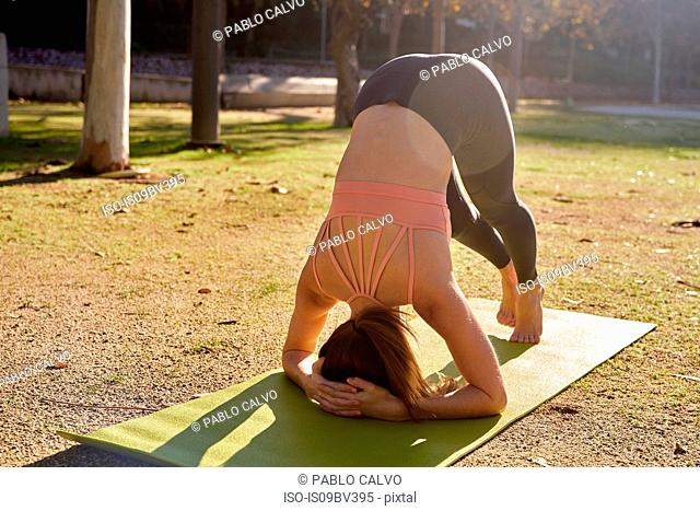 Woman practising yoga in city park