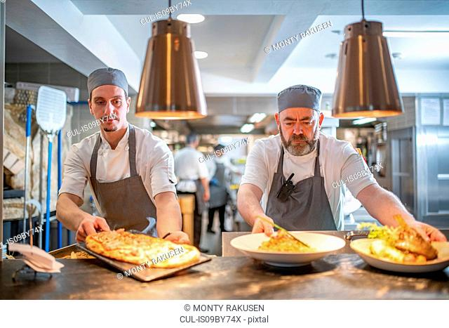 Chefs presenting dishes in Italian restaurant kitchen