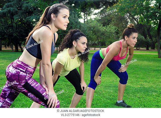 Young female athletes stretching before running in park