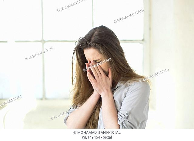 Young woman hiding face with hnads indoors