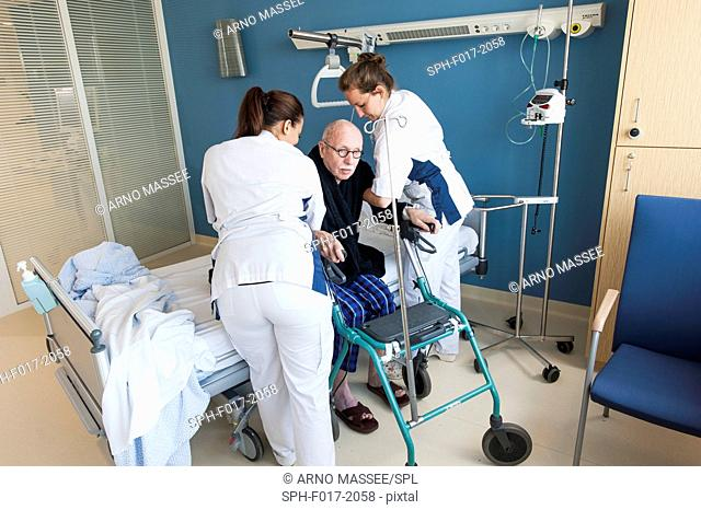 MODEL RELEASED. Female nurses helping senior male to sit down