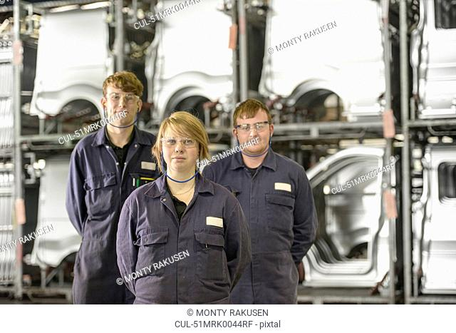 Apprentices standing in car factory