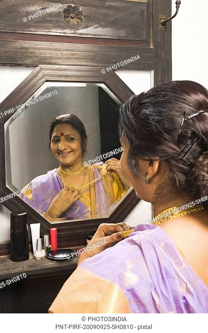 Woman getting dressed in front of a mirror