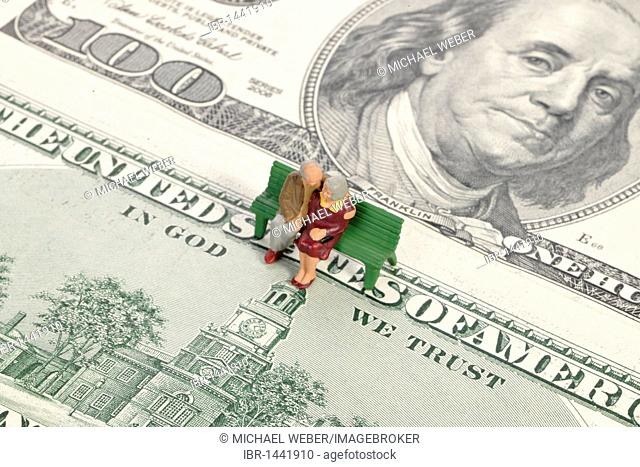 Pensioner miniature figures on 100-dollar bills, motto IN GOD WE TRUST, symbolic image for pension, retirement provisions