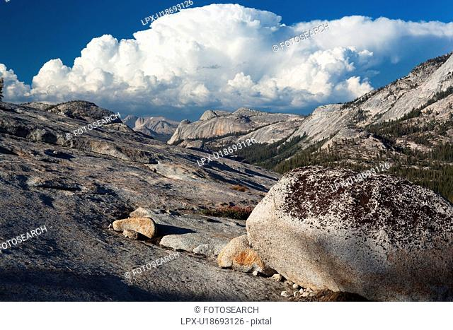 Panorama at Olmsted Point with erratics in foreground along granite ridge, and blue summer afternoon sky, with dramatic cloud formation, Yosemite