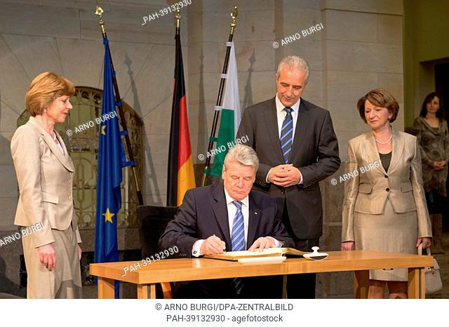 German president Joachim Gauck (2-L) signs a guest book at the State Chancellery in Dresden, Germany, 30 April 2013. Next to him stand his partner Daniela...