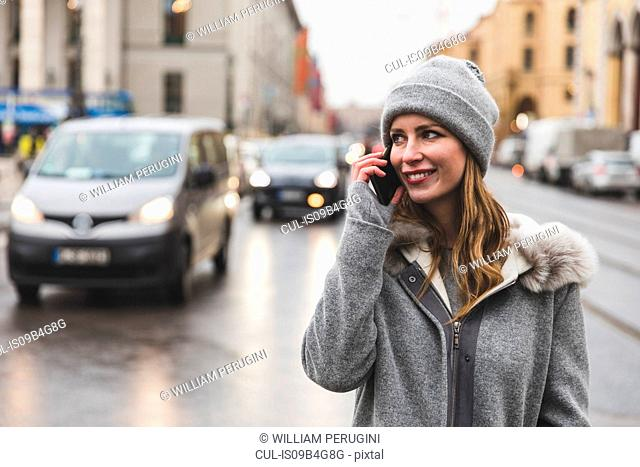 Mid adult woman in city making smartphone call