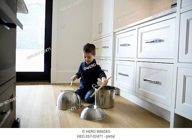 Boy banging on pots on kitchen floor