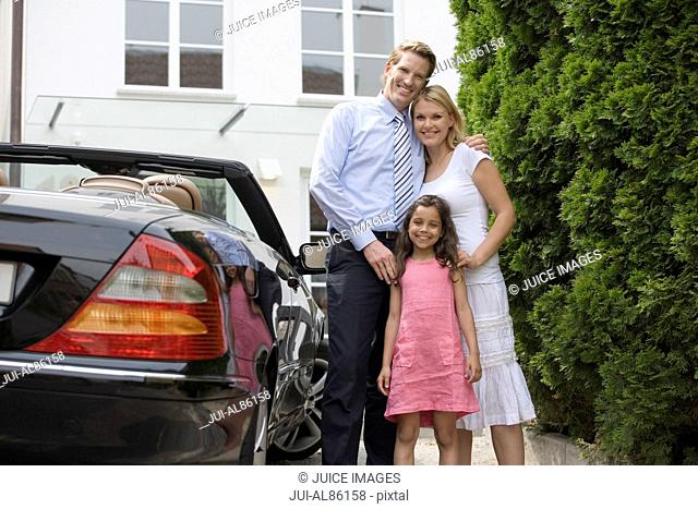 Portrait of family next to car