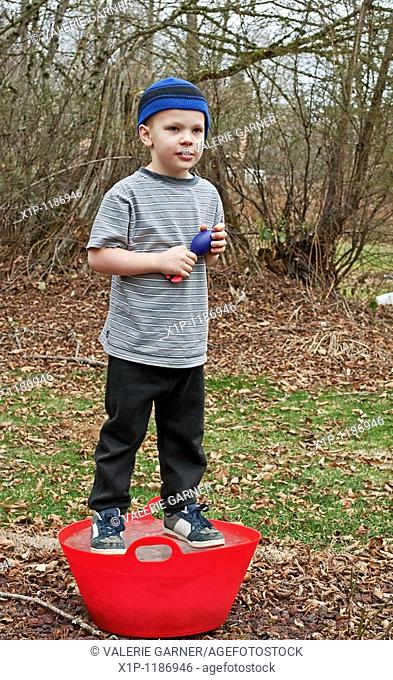 This Caucasian 5 year old boy is playing outside and standing on a red bucket that is frozen solid ice He's wearing a blue stocking cap