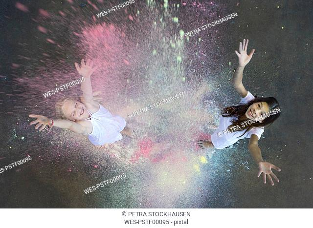 Two friends throwing colour powder in the air