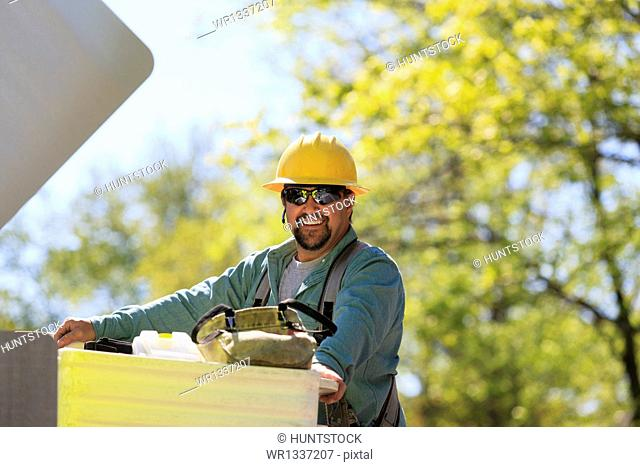 Power engineer preparing to ride in lift bucket, Braintree, Massachusetts, USA