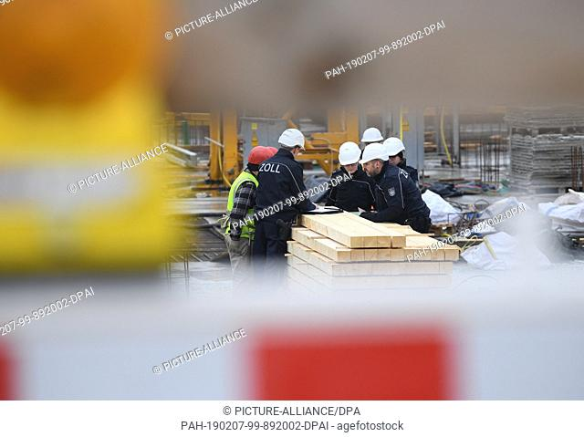 07 February 2019, Hessen, Frankfurt/Main: Customs officers inspect construction workers during a mission on a large construction site in the Niederrad district