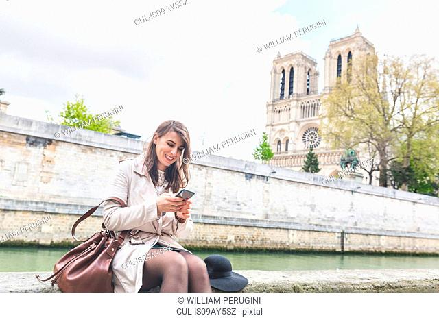 Young woman sitting reading smartphone on riverside at Notre Dame, Paris, France