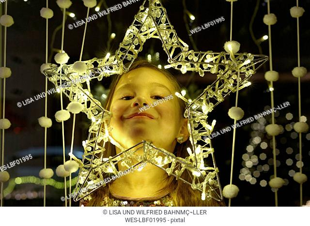 Portrait of smiling little girl looking through Christmas star