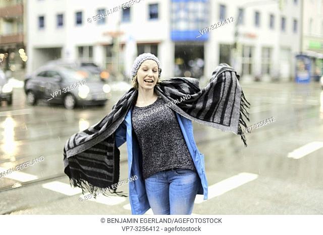funny woman playing with scarf outdoors in rain at street in city, Munich, Germany