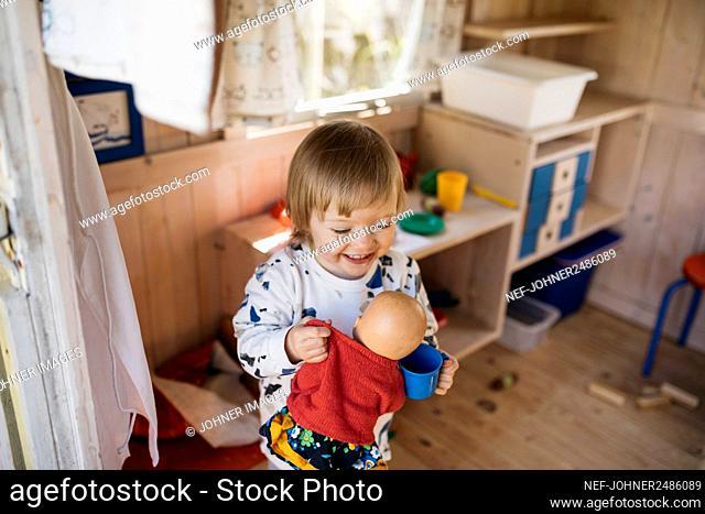 Toddler girl in playhouse
