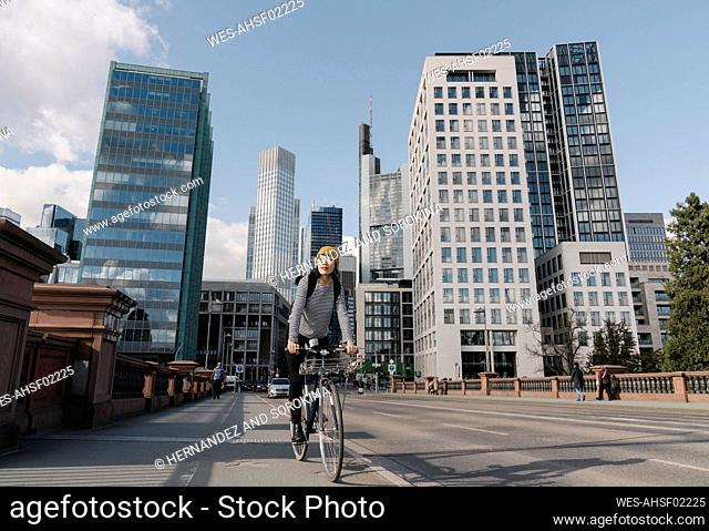 Woman riding bicycle in the city, Frankfurt, Germany
