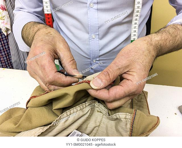 Tilburg, Netherlands. Hands of a Taylor mending a pair of trousers