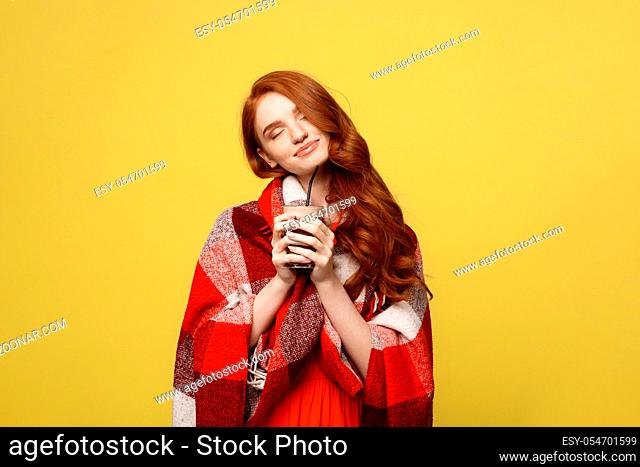 Lifestyle Concept: Portrait of woman basking with plaid and enjoy drinking chocolate Isolated over vivid yellow background