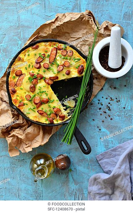 Paella in a pan with potatoes and sausages