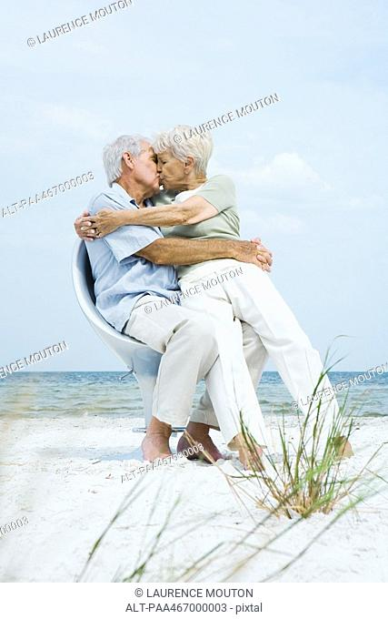 Senior couple sitting in chair together on beach, hugging and kissing, woman sitting on man's lap, full length