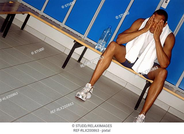 Afro-American in locker room resting after fitness training