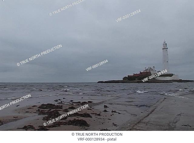 GV, Mwide shot of LA, lighthouse, sea lapping shore, calm, overcast. Whitley Bay, UK