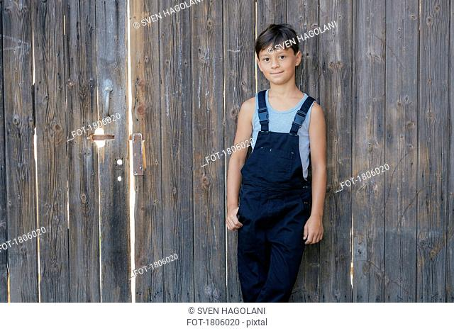 Portrait confident boy in overalls at wooden fence