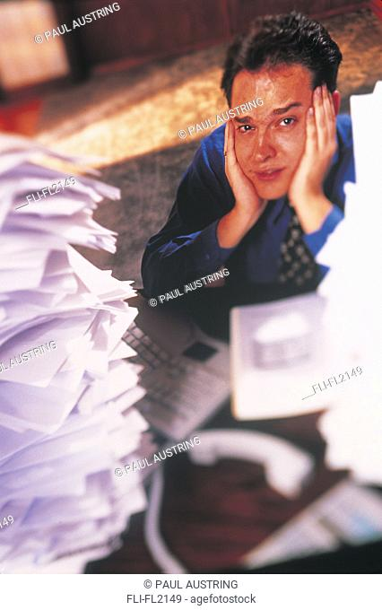 Male executive overwhelmed with piles of paperwork