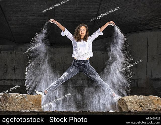 Young woman throwing flour while standing with legs apart on rocks under bridge