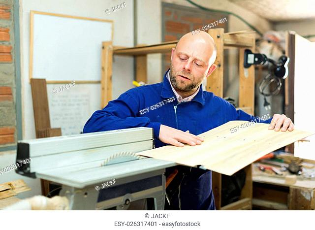 Portrait of woodworker working on a machine at wood workshop