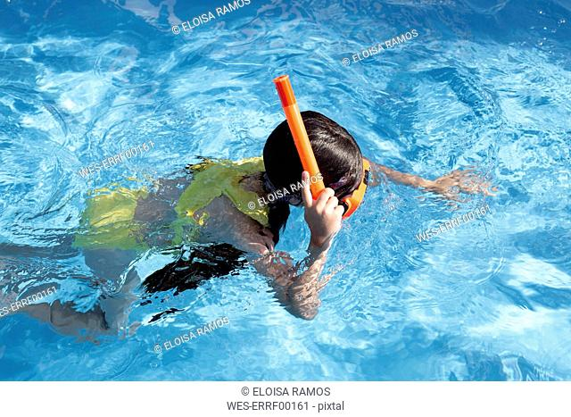 Lttle girl with snorkel and diving goggles in swimming pool