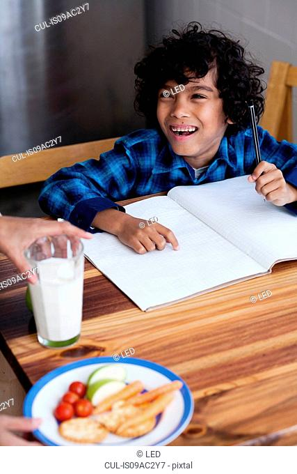 Boy doing homework, person serving snacks and milk