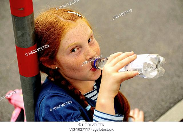 Girl sitting on the floor drinking a bottle of water. - GERMANY, 13/10/2008