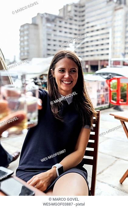 Young beautiful woman toasting with her friends on a terrace