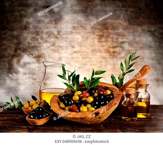 Freshly harvested olives berries in wood bowls and pressed oil in glass bottles. Still life of food preparation served on old wooden planks